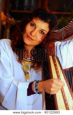 Young Woman Playing Celtic Harp In A Historical Costume
