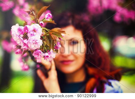 Young Woman Smelling A Beautiful Sakura Blossom, Pink Flowers