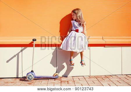 Cute Little Girl In White Dress And Scooter Against The Urban Colorful Wall