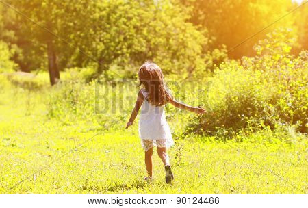 Silhouette Of A Little Girl Run On The Field On A Sunny Summer Day
