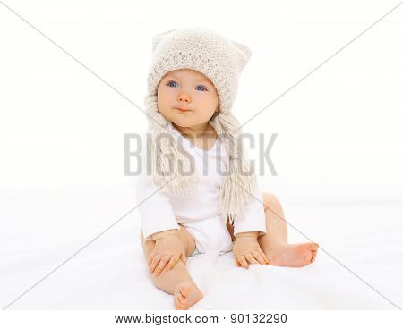 Portrait Of Cute Baby Sitting In White Knitted Hat