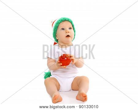 Christmas And Childhood Concept - Cute Baby In Bright Knitted Elf Hat With Red Apple And Looking U