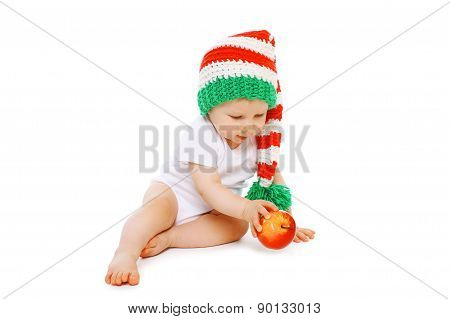 Christmas And Childhood Concept - Little Baby In Bright Knitted Gnome Hat With Red Apple
