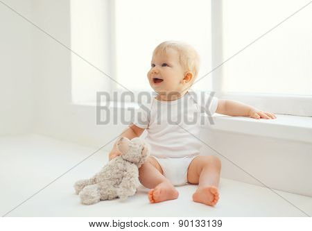 Cute Smiling Baby With Teddy Bear Toy Sitting At Home In White Room Near Window