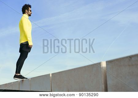 Sportsman in yellow wind breaker taking break with crossed hands standing on sky background