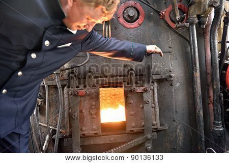 ST. PETERSBURG, RUSSIA - MAY 7, 2015: Machinist assistant opens the firebox of a steam locomotive. The parade of steam locomotives dedicated to the WWII Victory Day