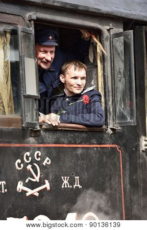 ST. PETERSBURG, RUSSIA - MAY 7, 2015: Machinists in the cab of steam locomotive during the parade dedicated to the WWII Victory Day. The event recreates the atmosphere of the postwar years