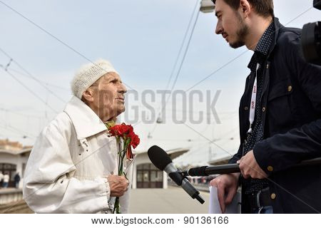 ST. PETERSBURG, RUSSIA - MAY 7, 2015: WWII veteran is interviewed by a journalist during the parade of steam locomotives. The event is dedicated to the WWII Victory Day