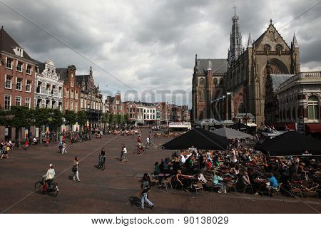 HAARLEM, NETHERLANDS - AUGUST 9, 2012: People walk in front of the Grote Kerk (Great Church) on the Grote Markt in Haarlem, North Holland, Netherlands.