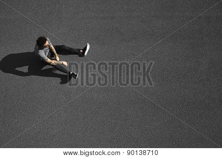 Jogging man taking a break during training outdoors in road
