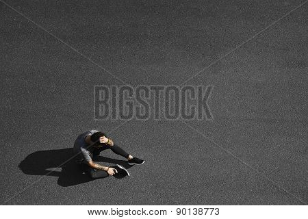 Sport Fitness Man Relaxing After Training. Young Male Athlete Resting Sitting In Asphalt