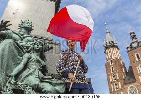 Woman with the Polish flag in the main square of Krakow, near the monument of Mickiewicz, St. Mary's Cathedral in the background.