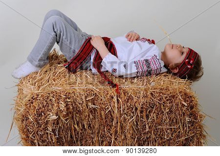 Ukrainian Girl In National Dress And Blue Jeans Lies On A Haystack.