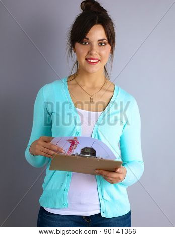 Young attractive fashion designer holding folders