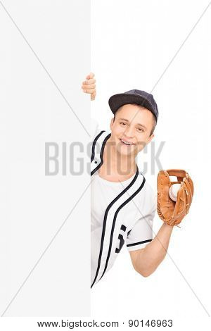 Male baseball player holding a ball with a baseball glove and posing behind a blank panel isolated on white background