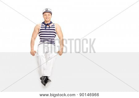 Young man in sailor outfit sitting on a blank white billboard isolated on white background