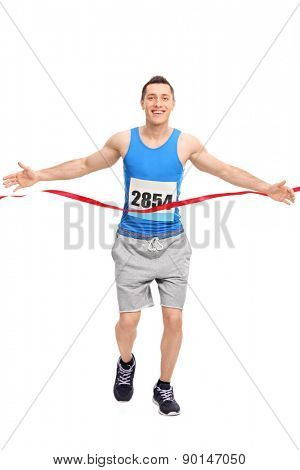 Full length portrait of a male runner with a race number on his chest, crossing the finish line isolated on white background