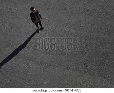 Muscular sportsman model ready for his run on a black asphalt.