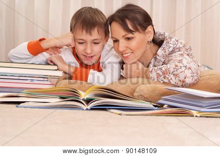 mother reading a book to kid boy