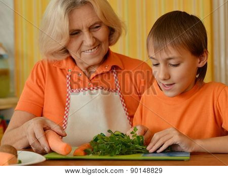Happy elderly woman and the boy in the kitchen