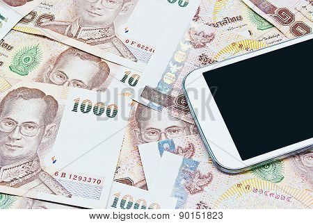 Smartphone with Thai money ready to travel on white background