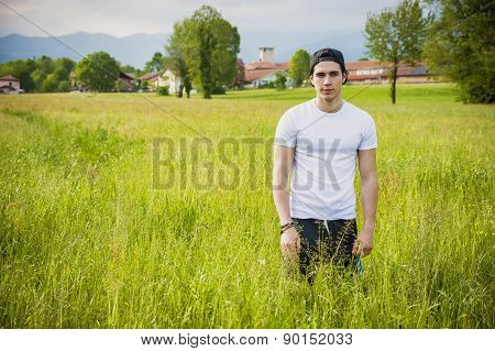 Handsome fit young man at countryside, in field or grassland