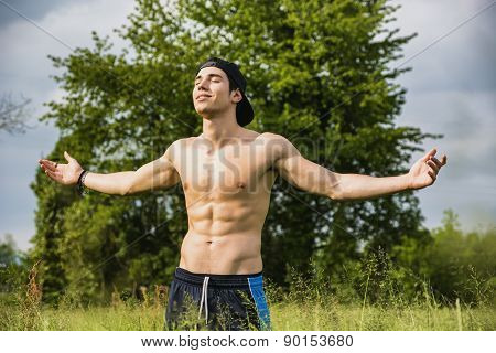 Shirtless young man celebrating nature at countryside