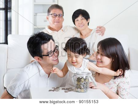 Toddler counting coins. Asian family money savings concept. Multi generations living lifestyle at home.