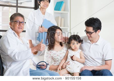 Pediatrician giving a thumb up after examined child. Pediatrician and patient healthcare concept.
