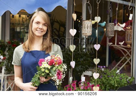 Florist Standing Outside Shop With Bunch Of Flowers