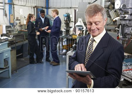 Owner Of Engineering Factory Using Digital Tablet With Staff In Background