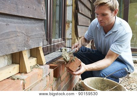 Construction Worker Laying Bricks On Site