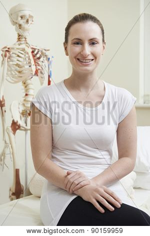 Portrait Of Female Osteopath In Consulting Room