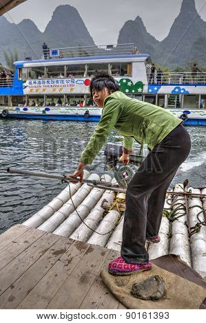 Asian Girl Ferryman Crosses River On Raft With Motor, China.