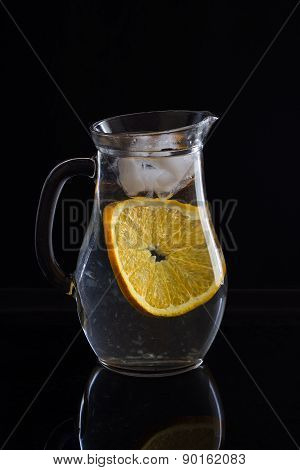 Jug With Water, Ice And One Slice Of Orange On Black Background