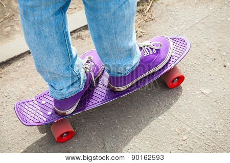 Riding Skateboarder Feet In A Blue Jeans