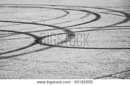 Dark Tire Tracks On Gray Asphalt Road
