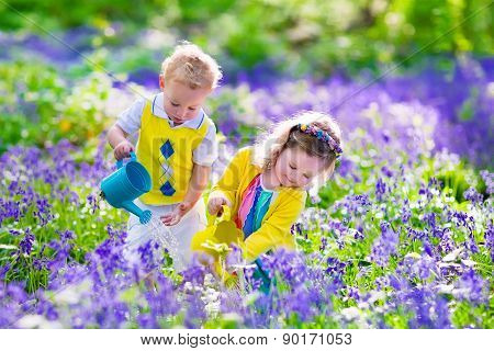 Children planting flowers, watering flower bed