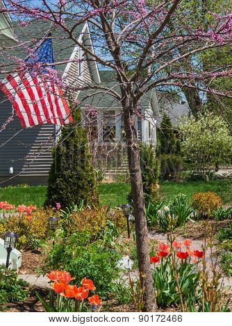 American flag flying in garden and house