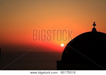 The sun setting over a church in Oia village, Santorini.
