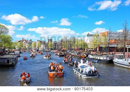 APRIL 27: Amsterdam canals full of boats and people in orange during the celebration of kings day on April 27, 2015 in Amsterdam, The Netherlands