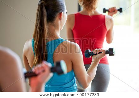 fitness, sport, training, people and lifestyle concept - close up of women working out with dumbbells and flexing muscles in gym