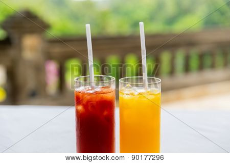 fruit and vegetable drinks concept - glasses of fresh orange and tomato juice at restaurant