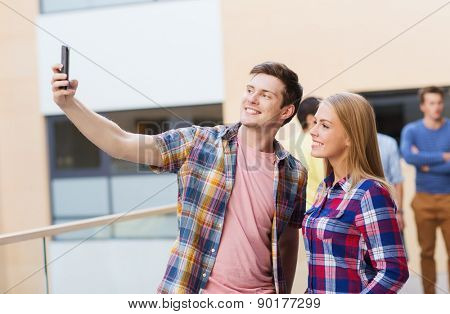 friendship, people, technology and education concept - group of smiling students with smartphone taking selfie outdoors