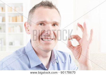 Smiling deaf man using sign language and showing OK sign