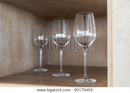 winery, glassware and alcohol concept - empty wine glasses set on shelf at restaurant