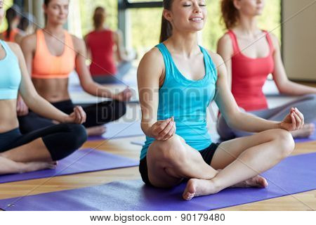 sport, meditation, yoga, people and lifestyle concept - group of happy women meditating on mat in gym