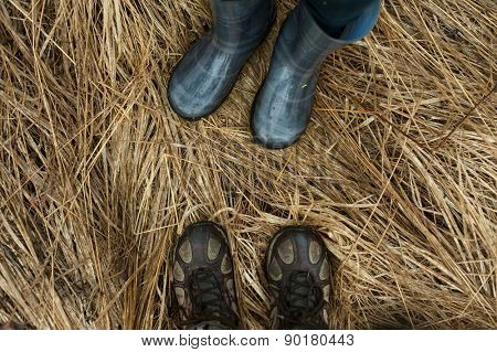 Man and woman feet wearing rubber boots and shoes outdoors