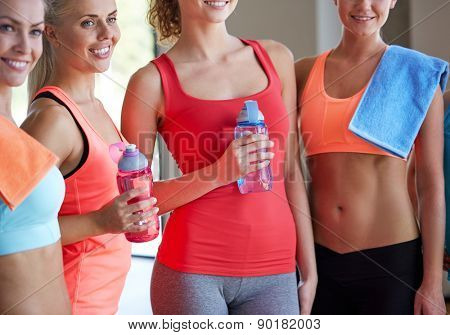 fitness, sport, teamwork, people and lifestyle concept - group of women with bottles of water in gym