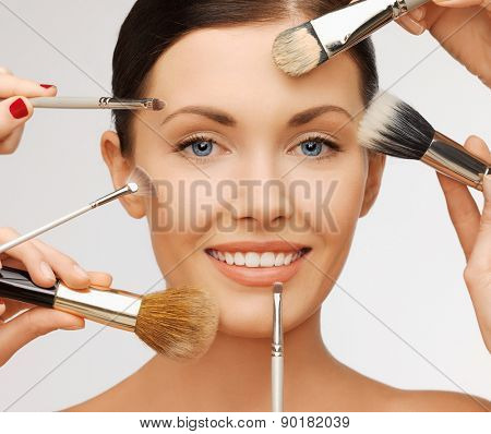 beauty and makeup concept - closeup portrait of beautiful woman getting professional make-up with many brushes